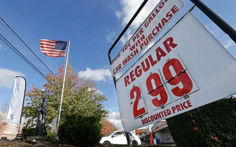 An American flag flies at a gas station advertising a discounted price for gas at $2.99 per gallon, with the purchase of a car wash, October 29, 2014, in Lynnwood, Washington.