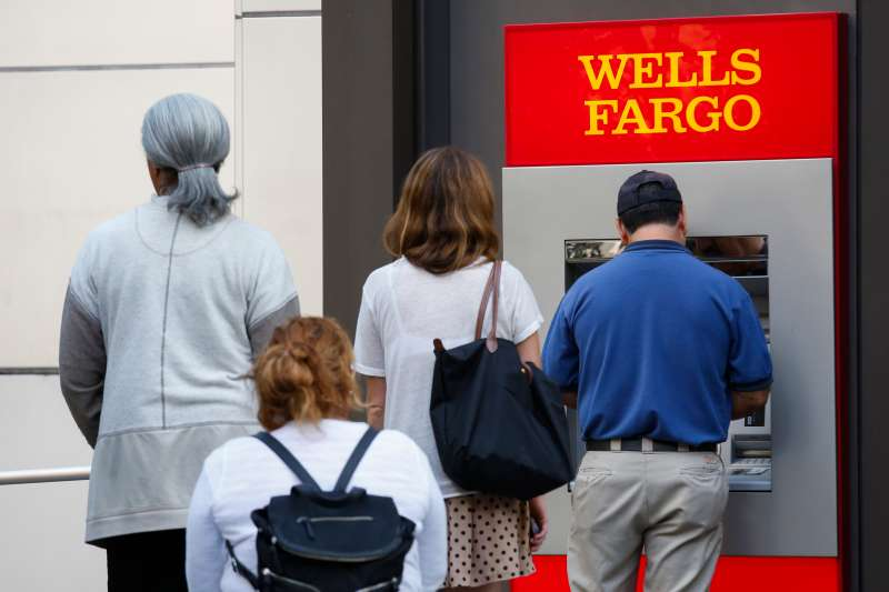 Customers wait in line for an ATM outside of a Wells Fargo & Co. bank branch in Los Angeles, California, U.S., on Tuesday, July 7, 2015.