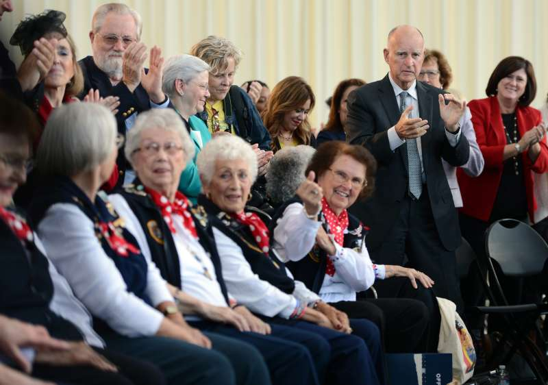 California Governor Jerry Brown applauds a group of former female factory workers from World War II after signing the Equal Pay Act into law on October 6, 2015 at the Rosie the Riveter National Monument in Richmond, Calif.