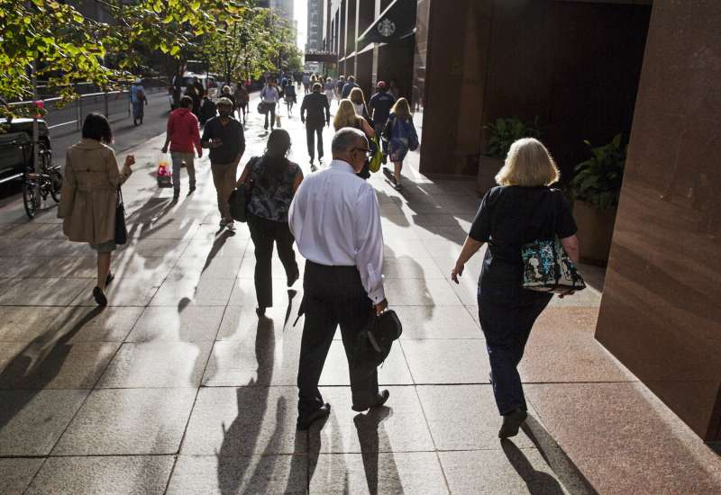 Commuters walk down a sidewalk lit by the rising sun in New York, September 29, 2015.
