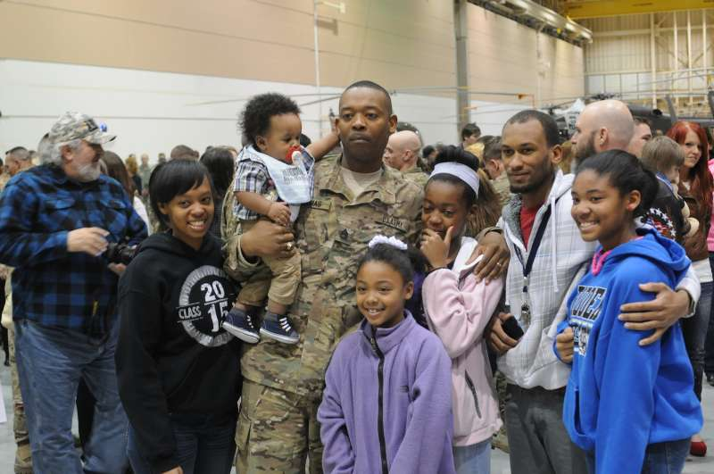 U.S. Army Sgt. 1st Class Ricky Thomas, 4th Brigade Special Troops Battalion, 4th Brigade Combat Team, 10th Mountain Division, poses for a picture with his family after returning to Fort Polk from Afghanistan February 11, 2014.
