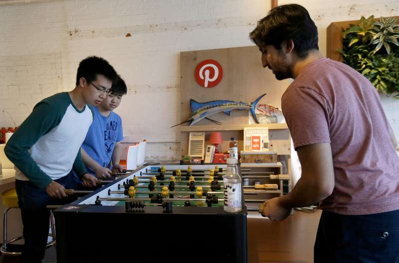 Pinterest software engineer interns Kevin Lau, from left, Charlie Gu and Neil Raina play foosball in the office in San Francisco, Wednesday, April 1, 2015. The San Francisco-based venture capital darling celebrated its fifth birthday in March 2015.