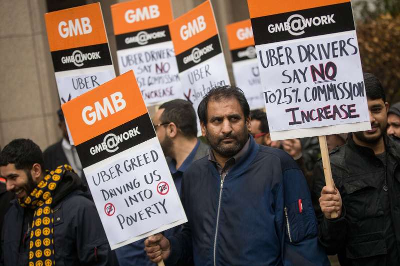 Uber drivers hold up signs during a protest against a rise in the commission taken by Uber.