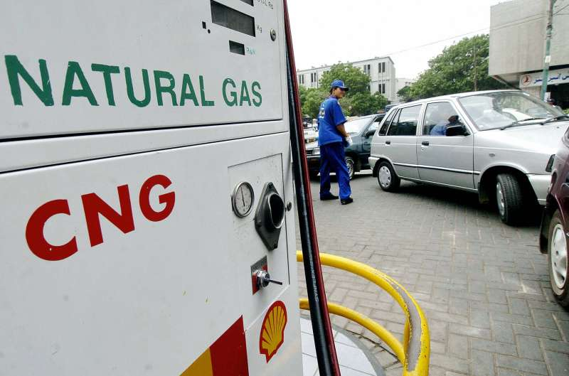 A Pakistani employee of a service station helps drivers to form a queue to fill their vehicles with Compressed Natural Gas (CNG) in Karachi, 04 July 2005.