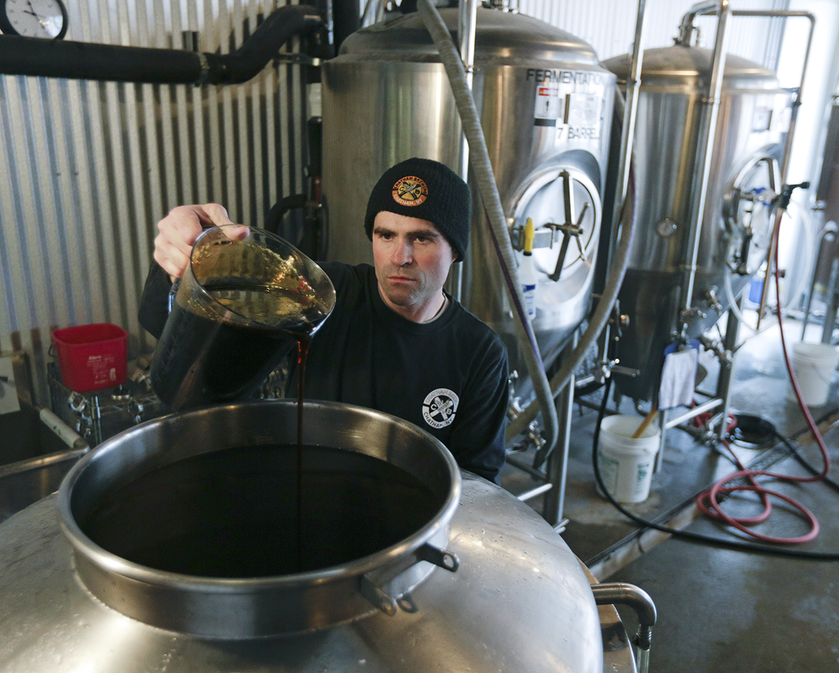 Brewer Matthew Perry adds maple syrup to a tank while making maple amber beer at Chatham Brewing in Chatham, N.Y.