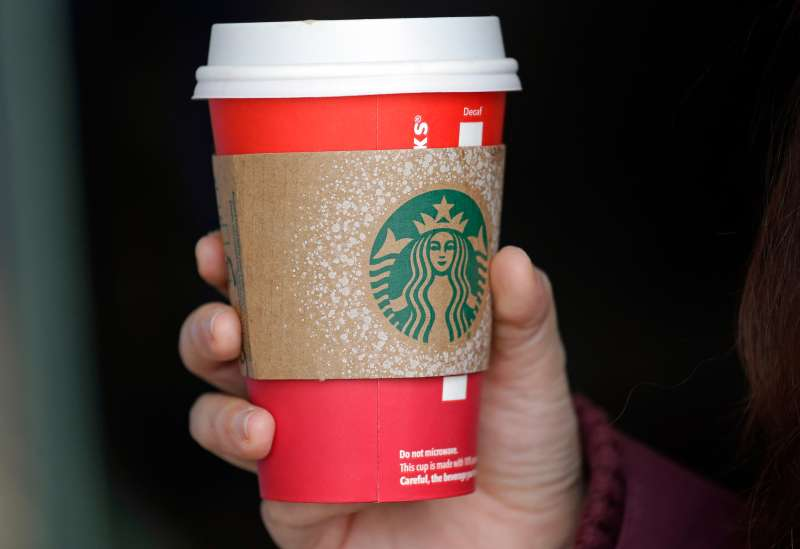 A customer carries a coffee drink in a red paper cup, with a cardboard cover attached, outside a Starbucks coffee shop in the Pike Place Market, November 10, 2015, in Seattle.