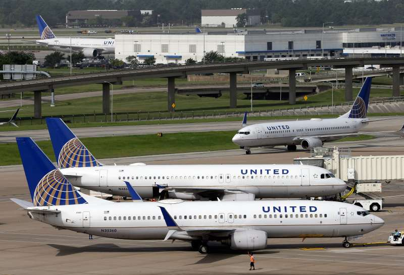 In this July 8, 2015 photo, a United Airlines plane, front, is pushed back from a gate at George Bush Intercontinental Airport in Houston.