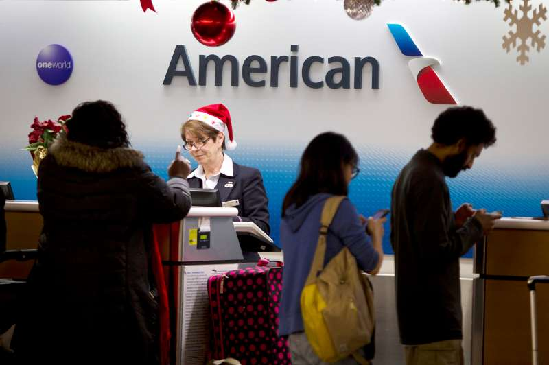 An agent for American Airlines checks in passengers while wearing a Santa hat on the day before Christmas at LaGuardia Airport in New York, December 24, 2014.