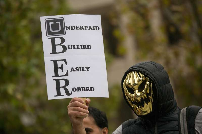 An Uber driver wearing a mask holds up a sign during a protest against a rise in the commission taken by Uber Technologies Inc. outside their offices in London, U.K., on Thursday, Nov. 12, 2015.
