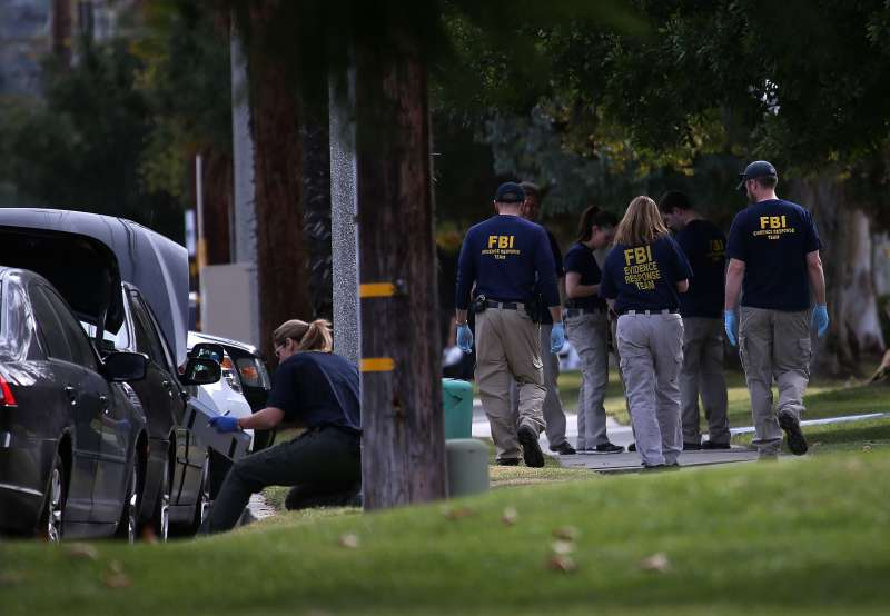 Members of the Evidence Response Team from the Federal Bureau of Investigation examine a car that allegedly belonged to Syed Farook on December 3, 2015 in Redlands, California.