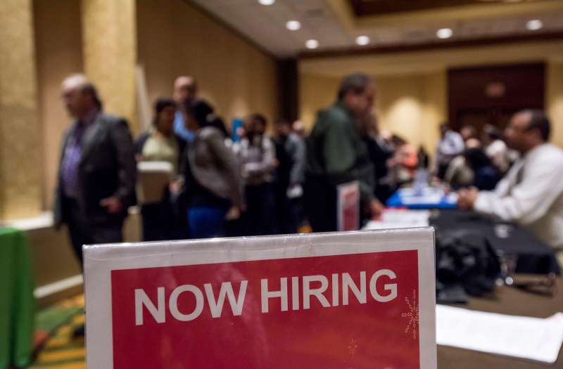 Now Hiring  signage is displayed as job seekers wait in line to enter the San Jose Career Fair in San Jose, California, on November 10, 2015.
