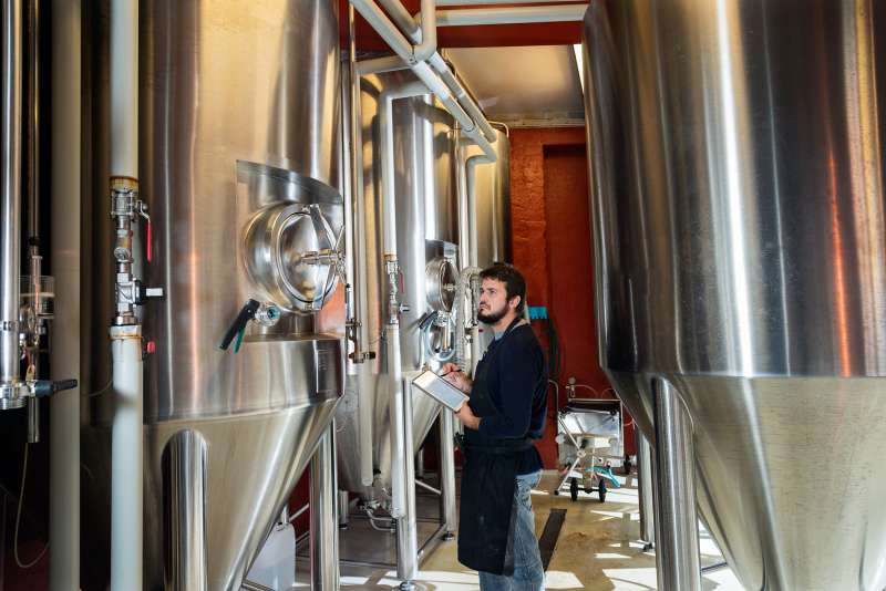 A brewmaster checks the brewery tanks.