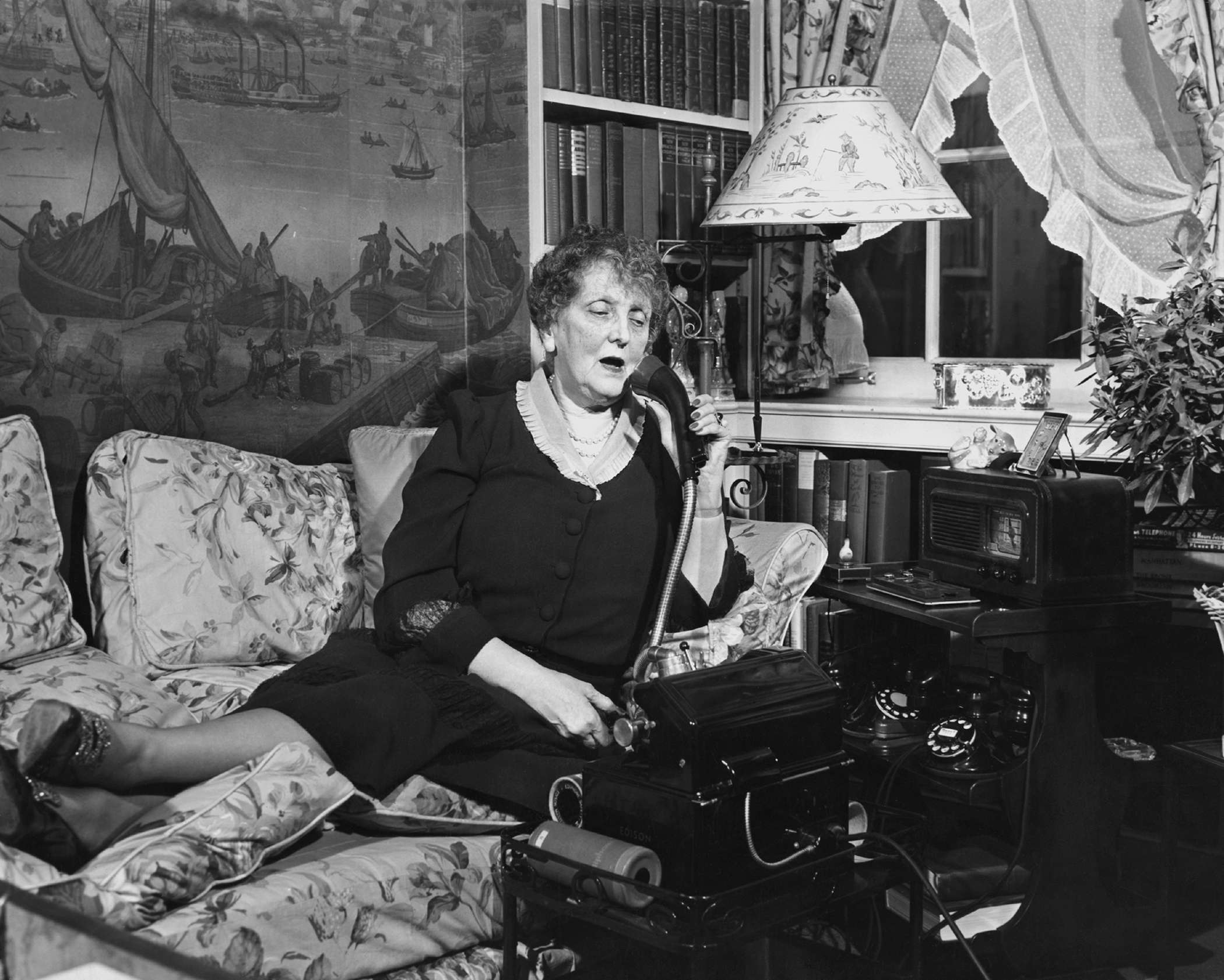 Writer Emily Post (1872-1960) pictured in her living room speaking on the telephone, USA, circa 1940.