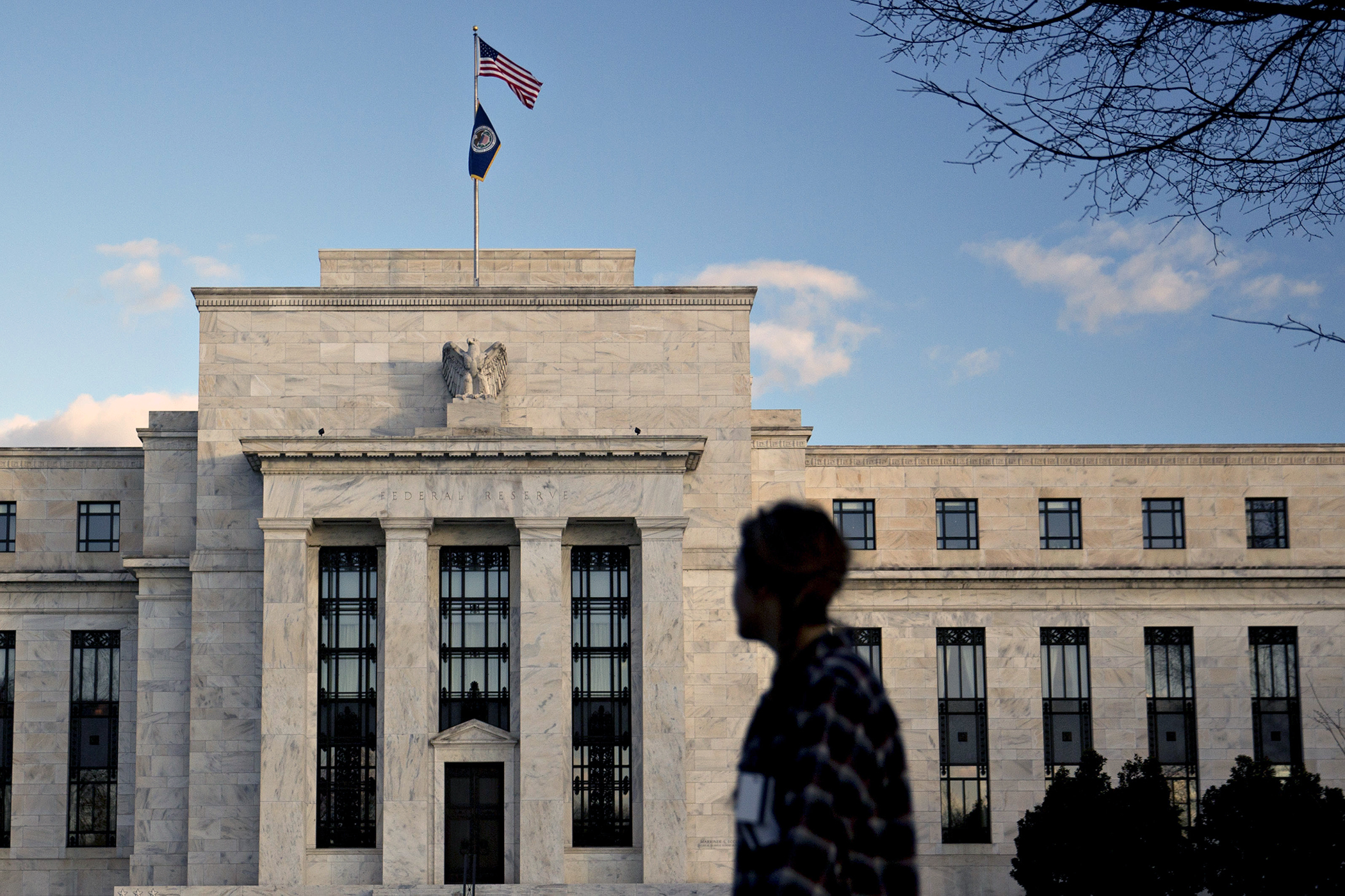 A pedestrian walks past the Marriner S. Eccles Federal Reserve building in Washington, D.C., on December 15, 2015.