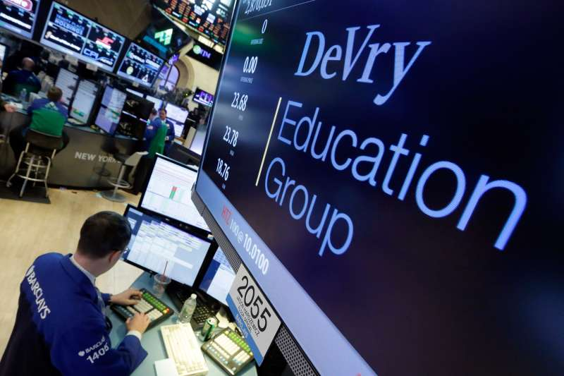 Specialist Neil Gallagher works at the post that handles DeVry Education Group, on the floor of the New York Stock Exchange, January 27, 2016. The government is suing the operators of the for-profit DeVry University, alleging they misled consumers about students' jobs and earnings prospects.
