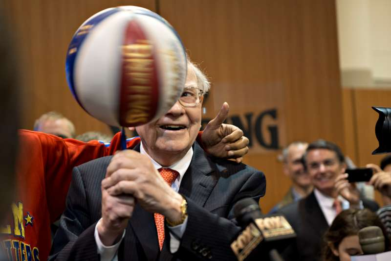 Warren Buffett, chairman and chief executive officer of Berkshire Hathaway Inc., spins a basketball on a pen as he stands with a member of the Harlem Globetrotters during a tour of the exhibition floor prior to the start of the Berkshire shareholders meeting in Omaha, Nebraska, U.S., on Saturday, May 4, 2013.