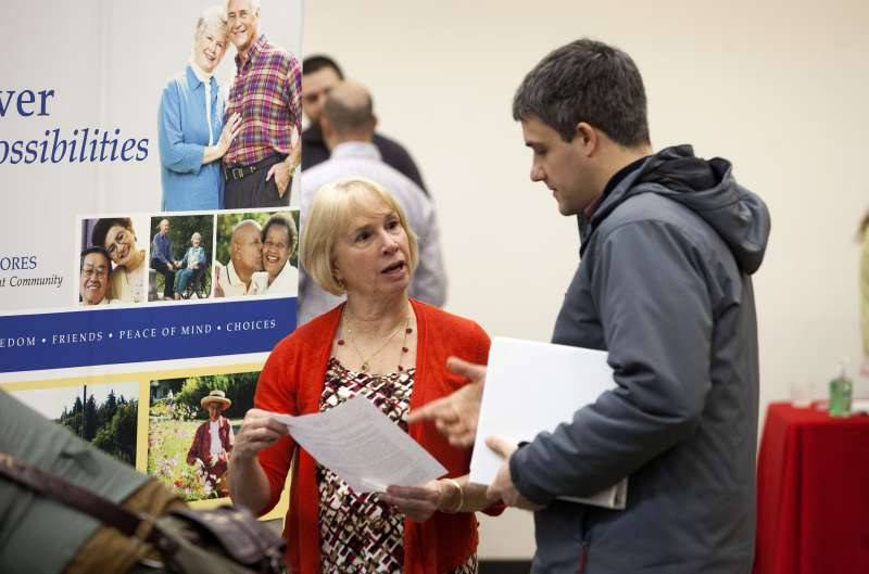 A job seeker, right, speaks with a company representative during a Choice Career Fair event in Seattle, Washington, U.S., on Thursday, Jan. 28, 2016.