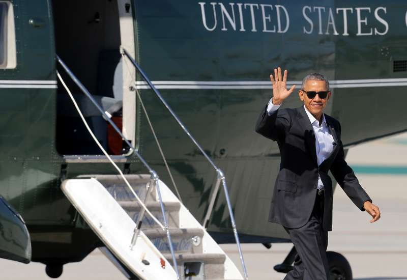 President Barack Obama waves to the assembled press as he arrives at Los Angeles International Airport aboard Marine One on February 12, 2016.