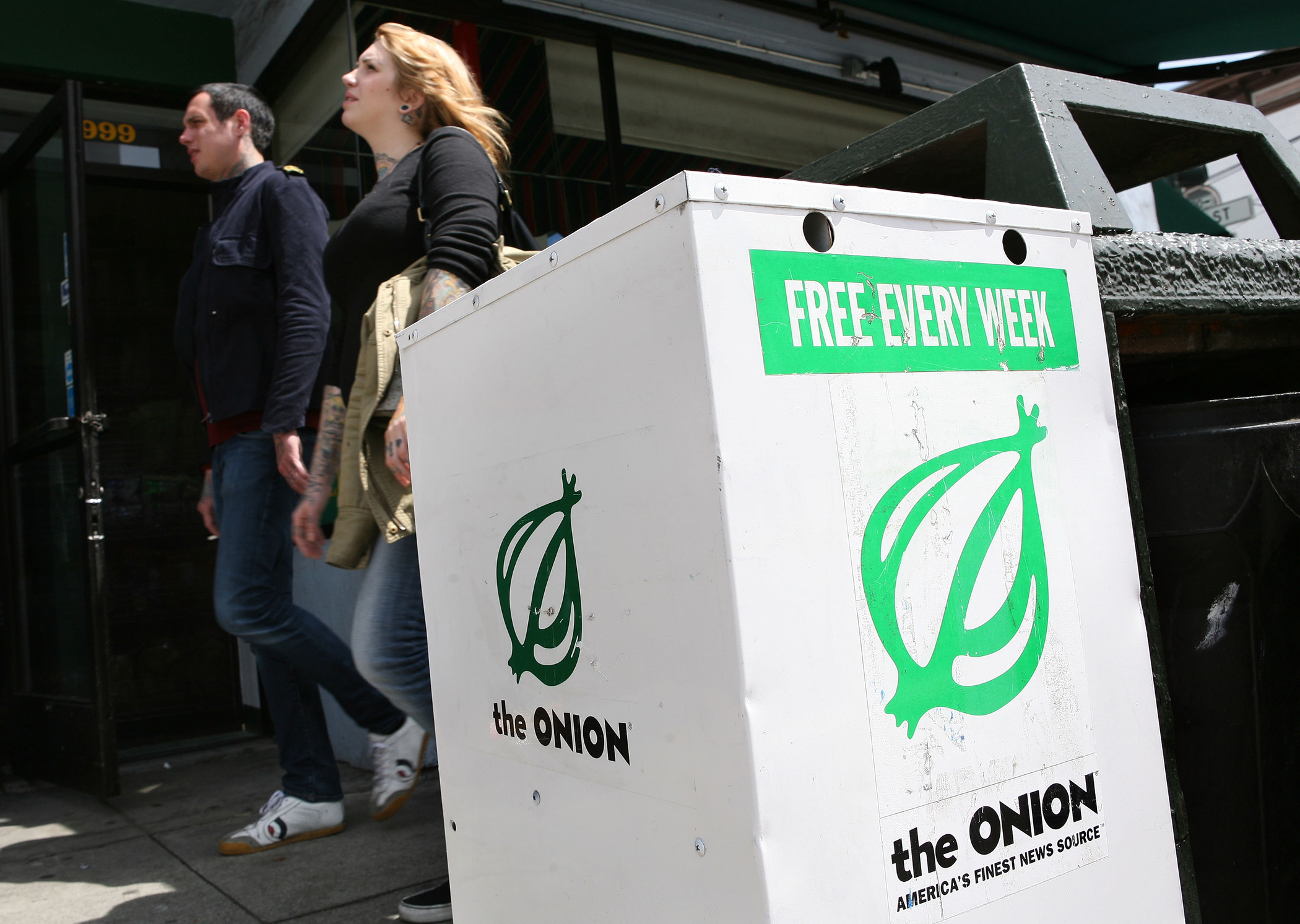 Pedestrians walk by an Onion news rack May 5, 2009 in San Francisco, California.