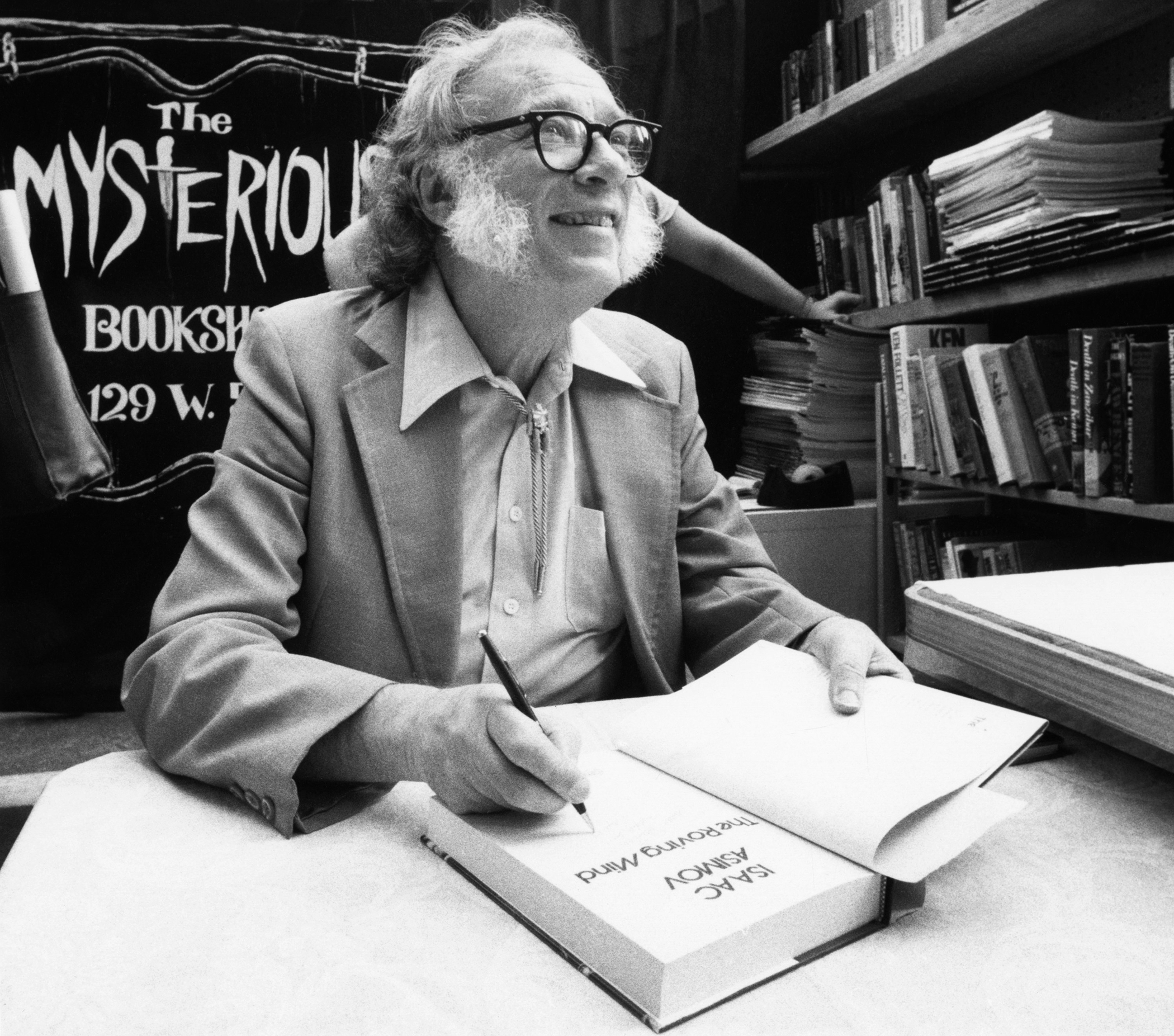 Author Isaac Asimov autographs books at the Mysterious Book Store stall on February 2, 1984 during the Fifth Avenue Book Fair held in New York City, United States.