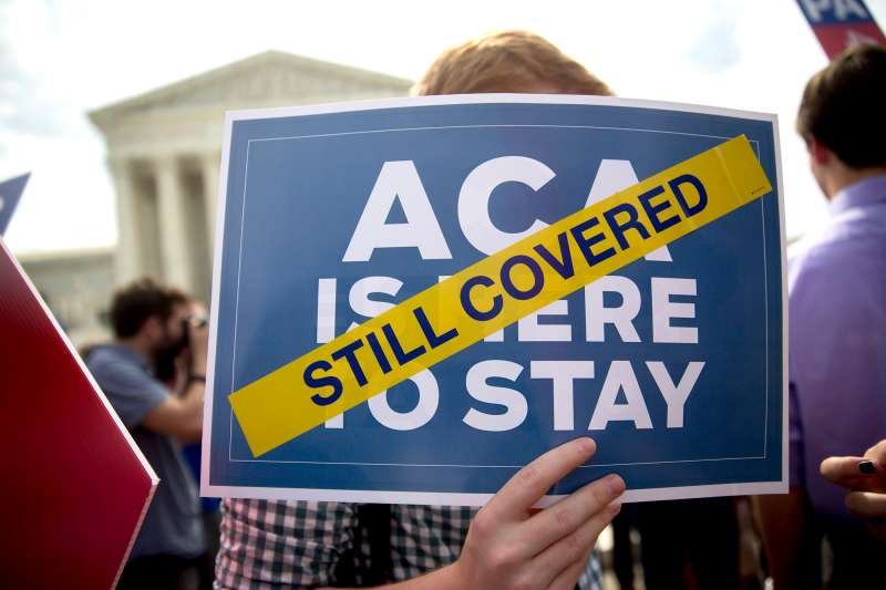the Affordable Care Act (ACA), holds an  ACA is here to Stay  sign