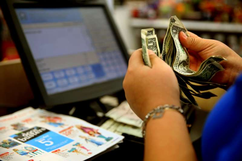 A cashier counts money from a customer at the register at Toys R Us on La Cienega Blvd in Los Angeles, Friday, November 27, 2015.