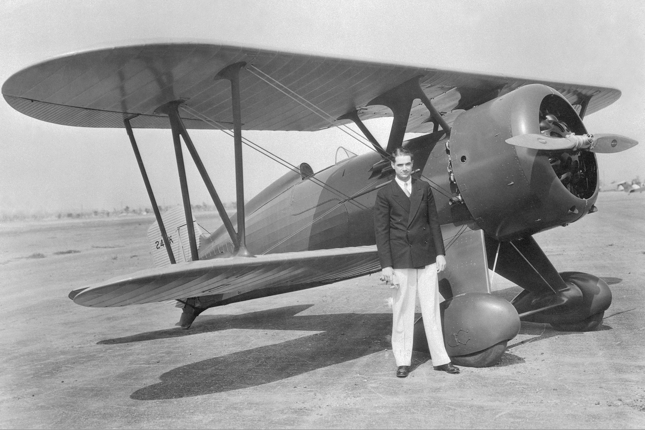 Howard Hughes, motion picture producer, shown after a test hop in his new high powered plane, a Boeing Army pursuit ship. Hughes is said to be the only private individual to own and pilot an Army plane.