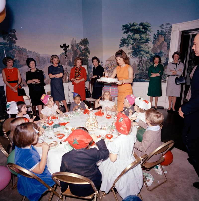 First Lady Jacqueline Kennedy carries Caroline Kennedy's cake to the table during a joint birthday party for Caroline and John F. Kennedy, Jr., in the President's Dining Room (Residence), White House, Washington, D.C., November 27, 1962.  Avery Hatcher, son of Associate Press Secretary, Andrew T. Hatcher, sits left of Caroline; Maria Shriver (with back to camera) sits at left in foreground.