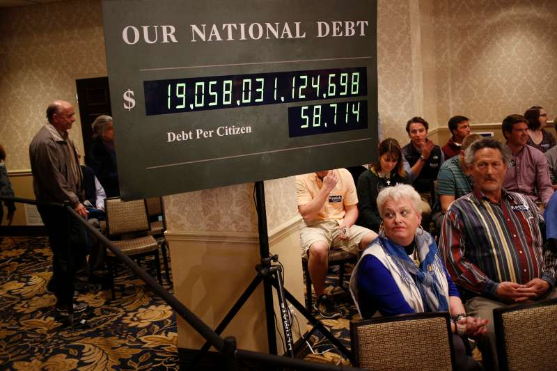 Attendees sit beneath a rendition of the U.S. national debt clock at an event for John Kasich, governor of Ohio and 2016 Republican presidential candidate, in Madison, Wisconsin, U.S., on Monday, March 28, 2016.