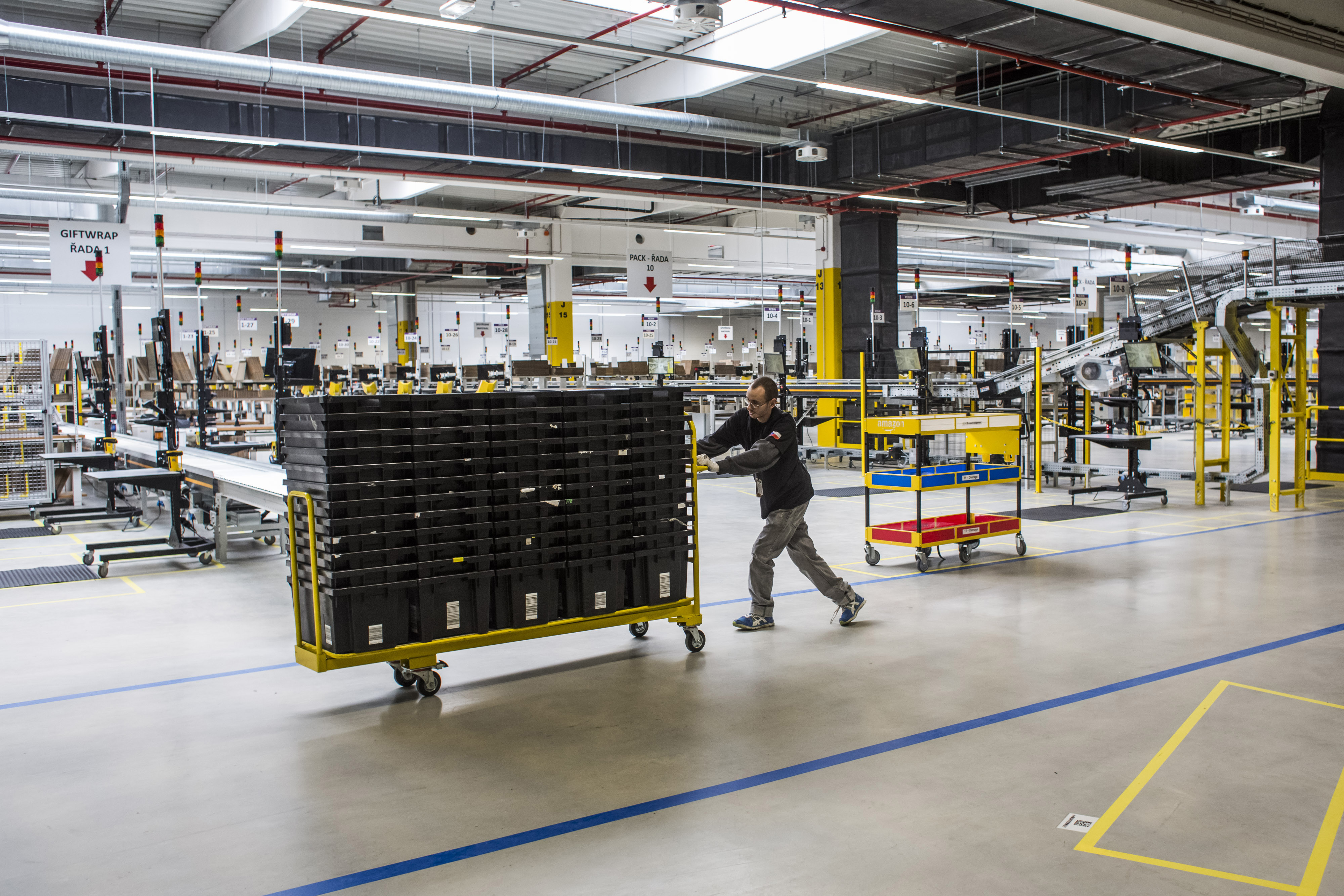 An employee moves a cart loaded with empty product crates through the shipping zone on the opening day of the new Amazon.Com Inc. fulfillment center in Dobroviz, Czech Republic, on Tuesday, Sept. 8, 2015.