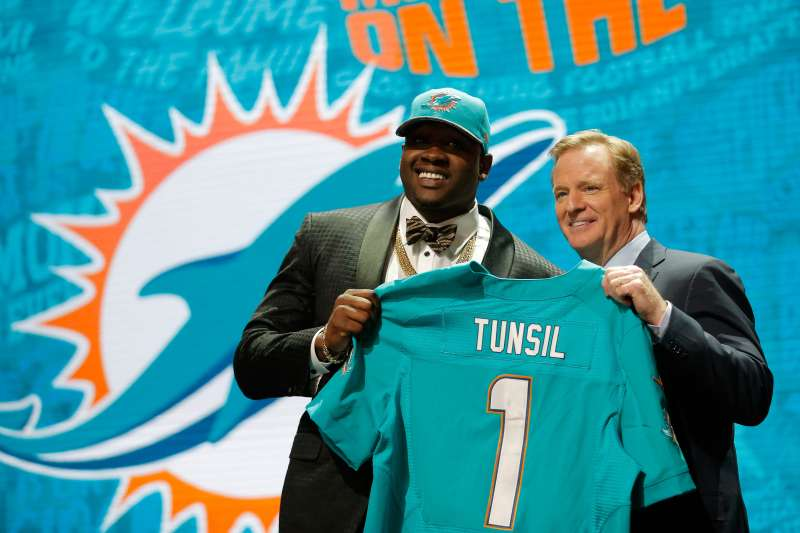 Laremy Tunsil of Ole Miss holds up a jersey with NFL Commissioner Roger Goodell after being picked #13 overall by the Miami Dolphins in the 2016 NFL Draft.