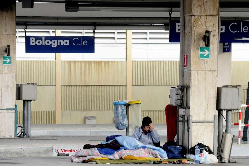 A homeless man sleeps at Bologna main railway station, Bologna, Italy, December 31, 2015.