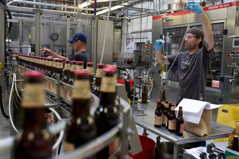 Employees work on the bottling line at the Dogfish Head Craft Brewery Inc. facility in Milton, Delaware, on June 22, 2011.