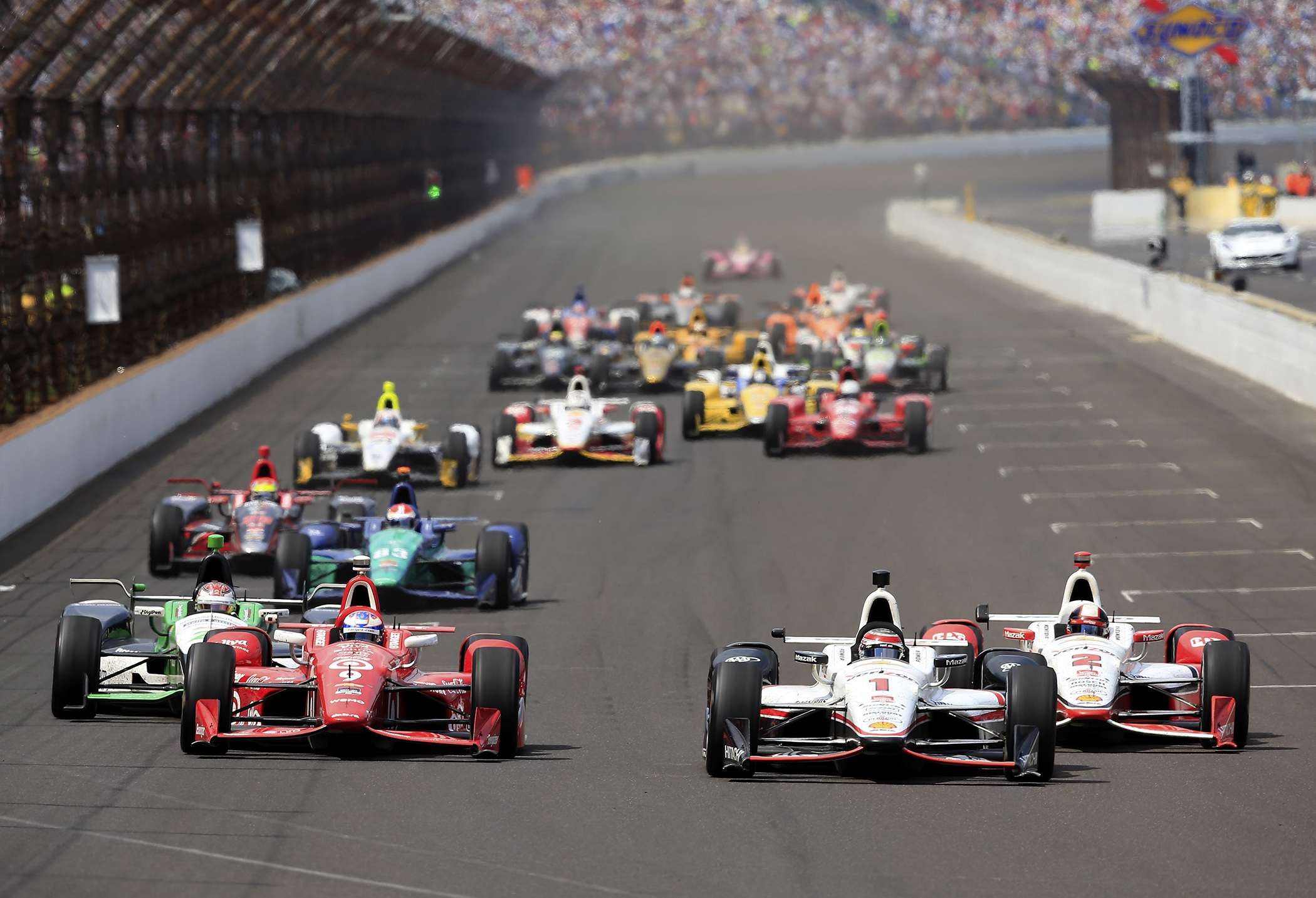 Scott Dixon of Australia, driver of the #9 Target Chip Ganassi Racing Chevrolet Dallara, races alongside Juan Pablo Montoya of Columbia, driver of the #2 Team Penske Chevrolet Dallara, and Will Power of Australia, driver of the #1  Verizon Team Penske Chevrolet Dallara, after a restart during the 99th running of the Indianapolis 500 at Indianapolis Motorspeedway on May 23, 2015 in Indianapolis, Indiana.