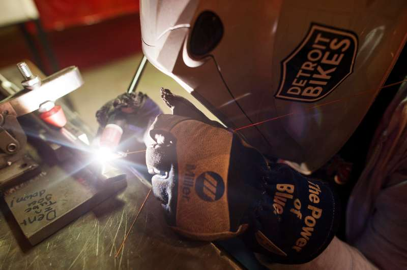 A worker tack welds parts of a bicycle frame together at the Detroit Bikes manufacturing facility in Detroit, Michigan, U.S., on Thursday, June 25, 2015.