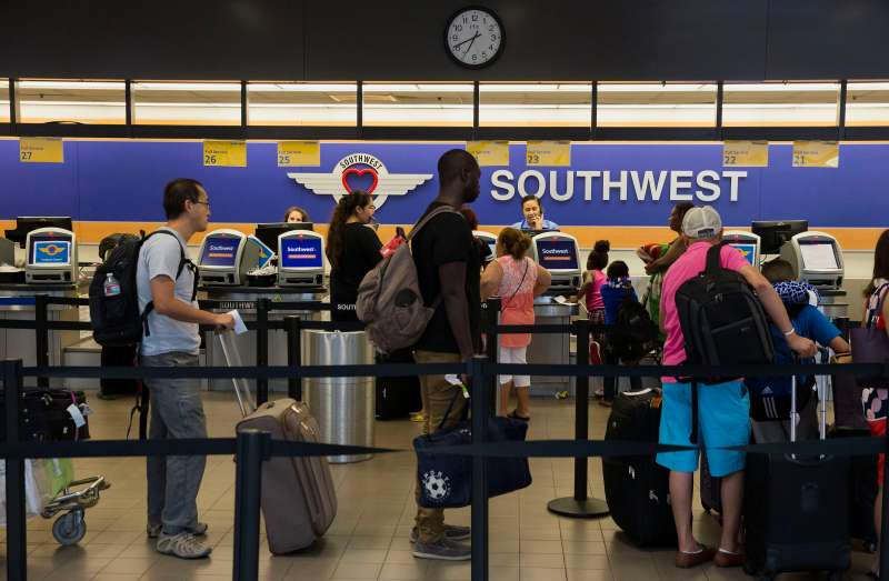 Travelers wait to check bags with Southwest Airlines Co. ticket counters in Terminal 1 of Los Angeles International Airport (LAX) in Los Angeles, California, U.S., on Tuesday, Aug. 18, 2015.