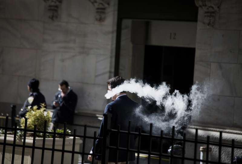 A trader smokes an electronic cigarette.