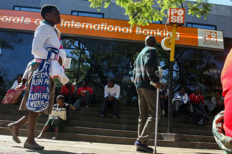 Zimbabweans queue to withdraw cash outside a bank.