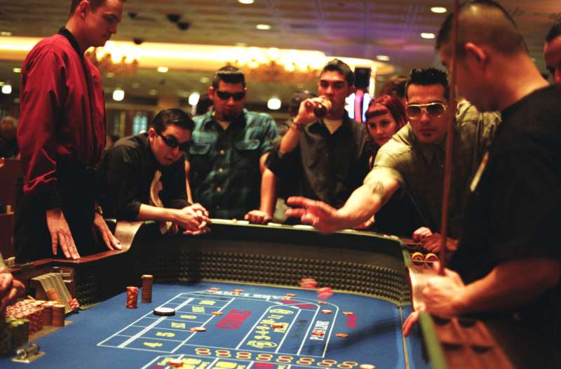 Group playing the tables at a casino, one man wearing Elvis style sunglasses, Las Vegas, USA, 2000s.