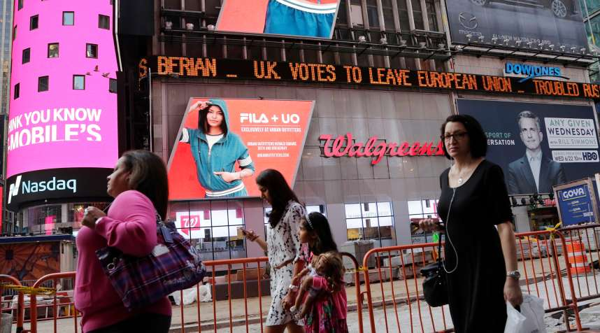 People walk past a news ticker that reads  U.K. Votes to Leave European Union,  Friday, June 24, 2016, in New York's Times Square. Britain voted to leave the European Union after a bitterly divisive referendum campaign, sending global markets plunging, casting British politics into disarray.
