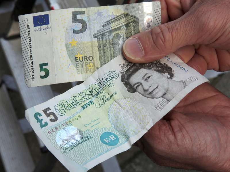 A 5-pound (bottom)and a 5-euro bill are held up in London, Britain, June 24, 2016. In a referendum on June 23, Britons have voted by a narrow margin to leave the European Union (EU).