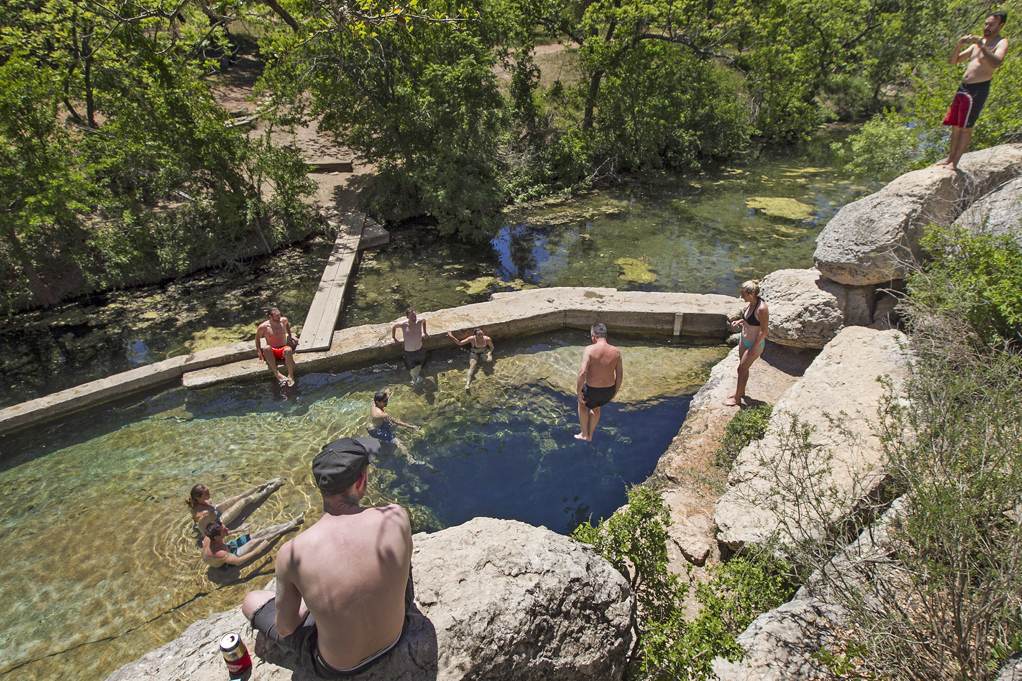 Visitors to Hays County's Jacob's Well Natural Area look on as a man leaps from the bluffs, aiming for the 12-foot cave opening though it is against park rules, in Wimberley, Texas, on Wednesday, April 30, 2014.