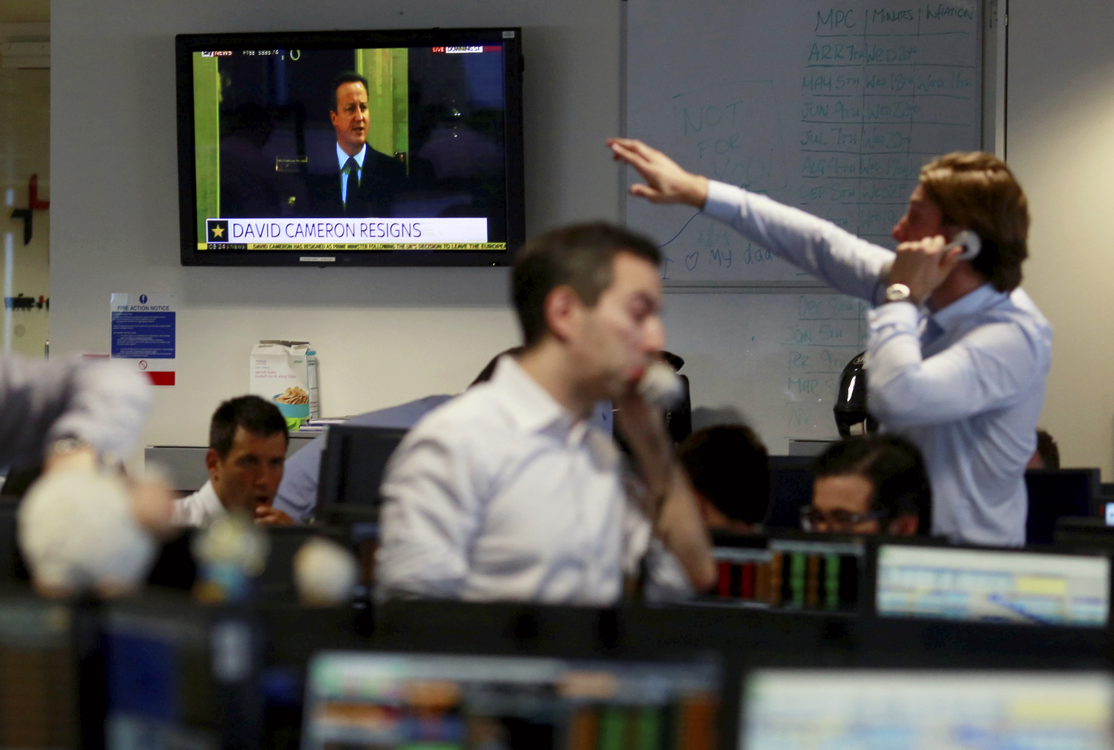 A TV shows the resignation of Britain's Prime Minister David Cameron as traders from BGC, a global brokerage company in London's Canary Wharf financial centre react after European stock markets opened June 24, 2016 after Britain voted to leave the European Union in the EU BREXIT referendum.