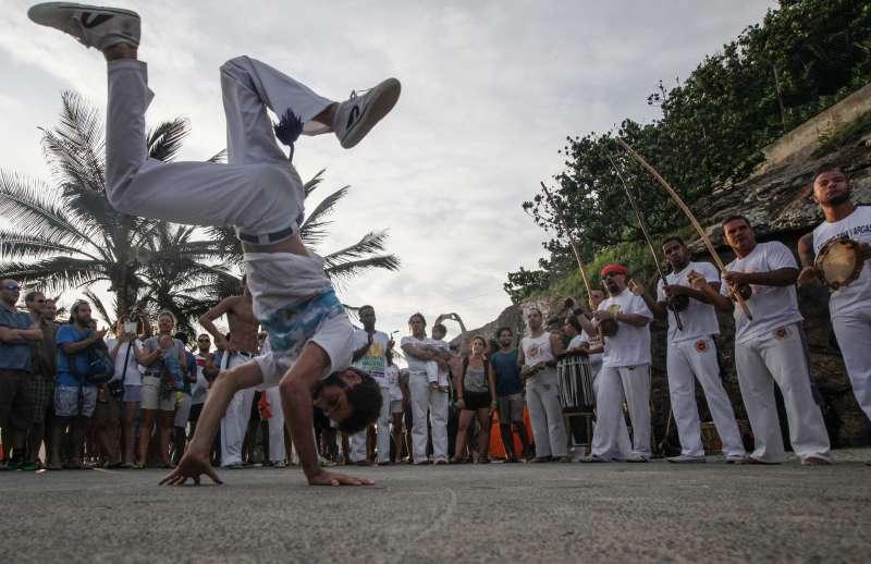 People gather to watch a capoeira performance along Arpoador rock, a popular tourist destination in Rio next to Ipanema beach, on February 28, 2016 in Rio de Janeiro,