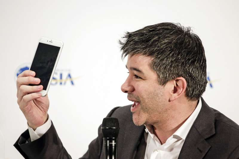 Travis Kalanick, co-founder and chief executive officer of Uber Technologies Inc., holds up a smartphone.