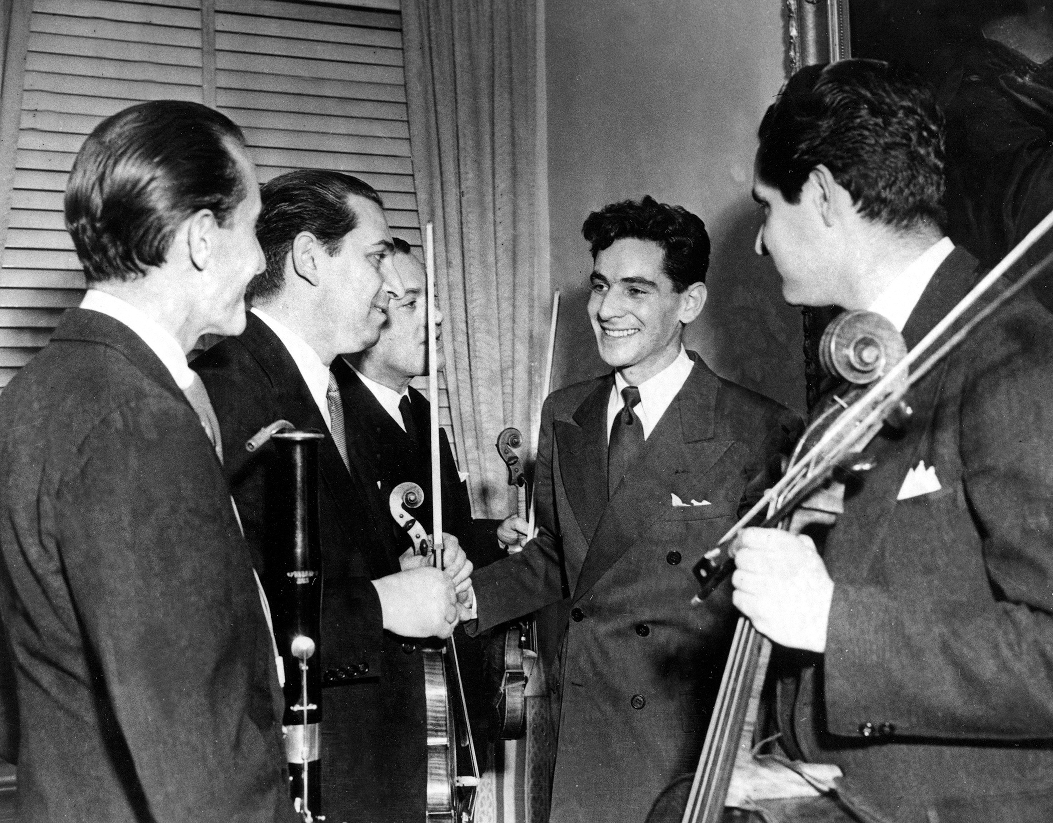 Leonard Bernstein, second from right, Assistant Conductor of the New York Philharmonic-Symphony Orchestra, is congratulated by members of the orchestra after the 25-year-old musician made his debut at Carnegie Hall in New York, Nov. 14, 1943. Bernstein substituted for Bruno Walter, who had become ill, to lead the organization in a 90-minute national radio broadcast.