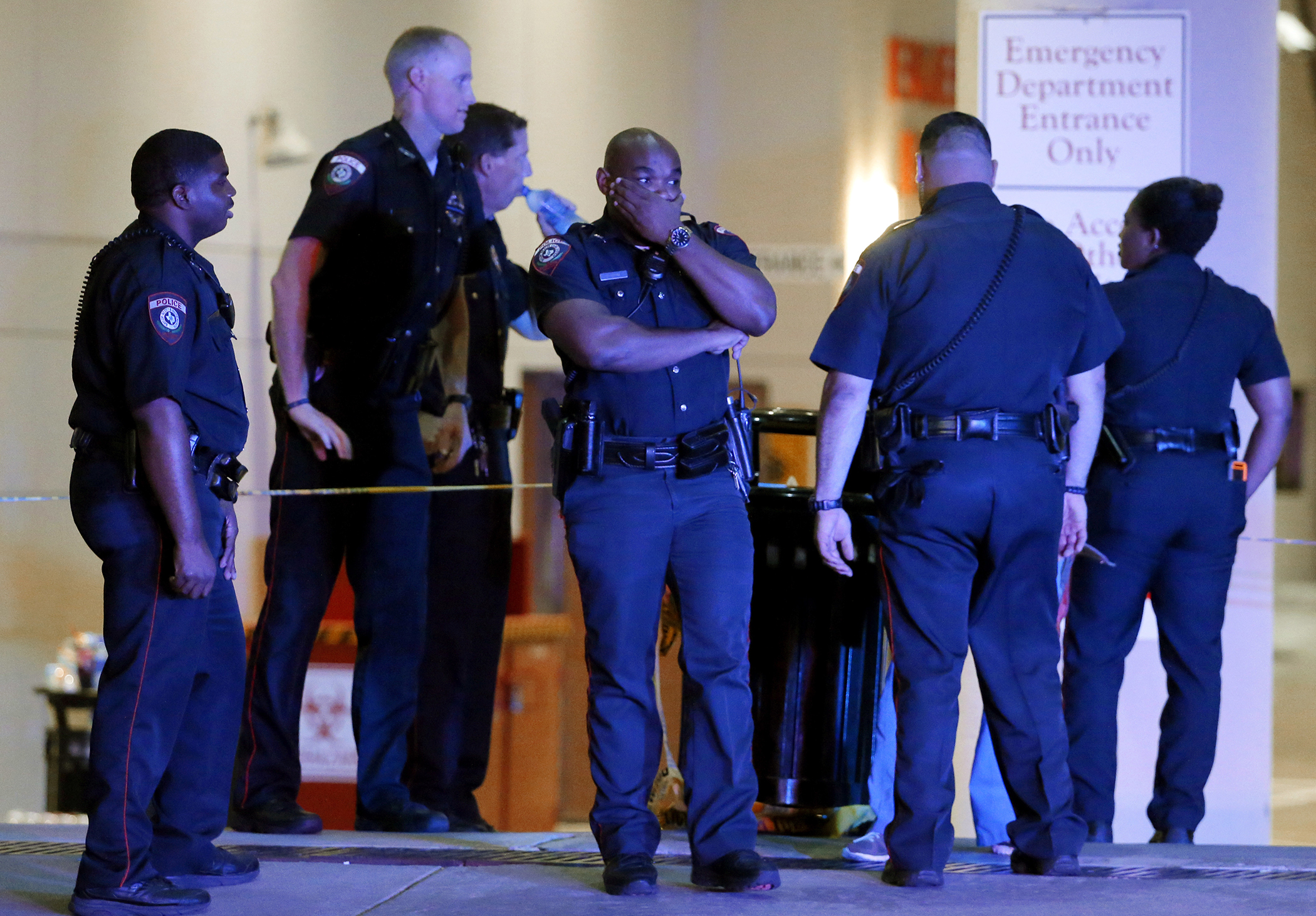 A Dallas police officer covers his face as he stands with others outside the emergency room at Baylor University Medical Center, Friday, July 8, 2016, in Dallas. Snipers opened fire on police officers in the heart of Dallas on Thursday night, killing some of the officers.