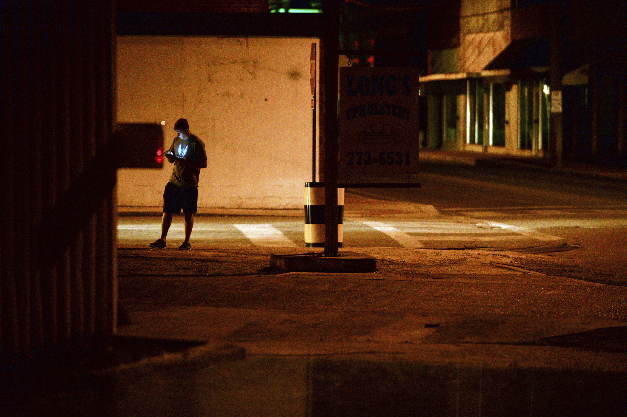 A teenagers plays  Pokemon Go  in downtown Hartselle, Alabama, at night on  July 13, 2016.