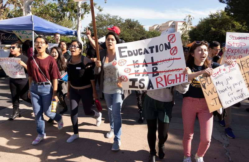 University of California at Irvine students hold signs in protest of high education costs during the Million Student March in Irvine, Calif., on Nov. 12, 2015.