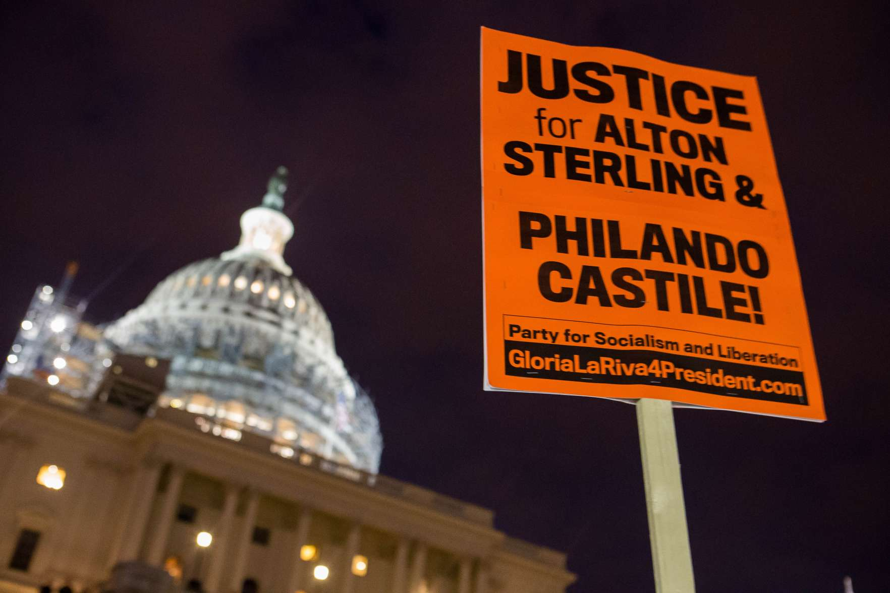 A demonstrator holds a sign outside of The Capitol Building after marching from The White House on July 7, 2016 in Washington, DC.  Protestors gathered in Washington to protest the fatal police shootings of Alton Sterling and Philando Castile.